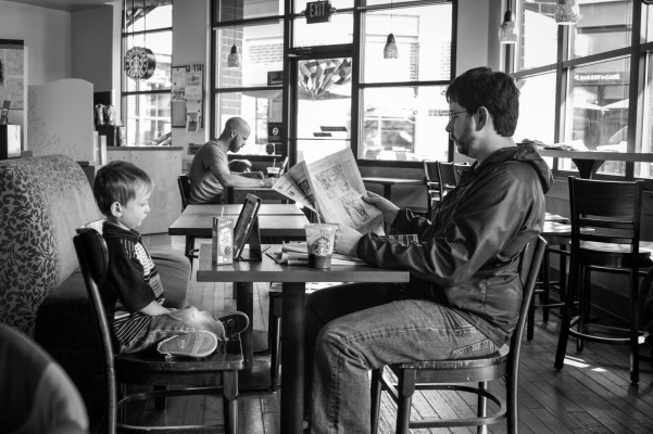Boy and his dad sitting in coffeeshop with iPad and newspaper