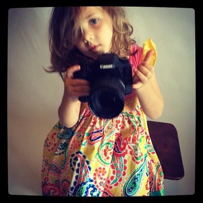 little girl holding a big DSLR camera