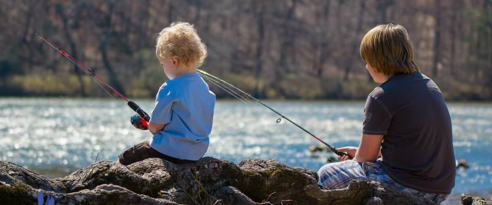 two little boys sitting on rocks and roots fishing in a river