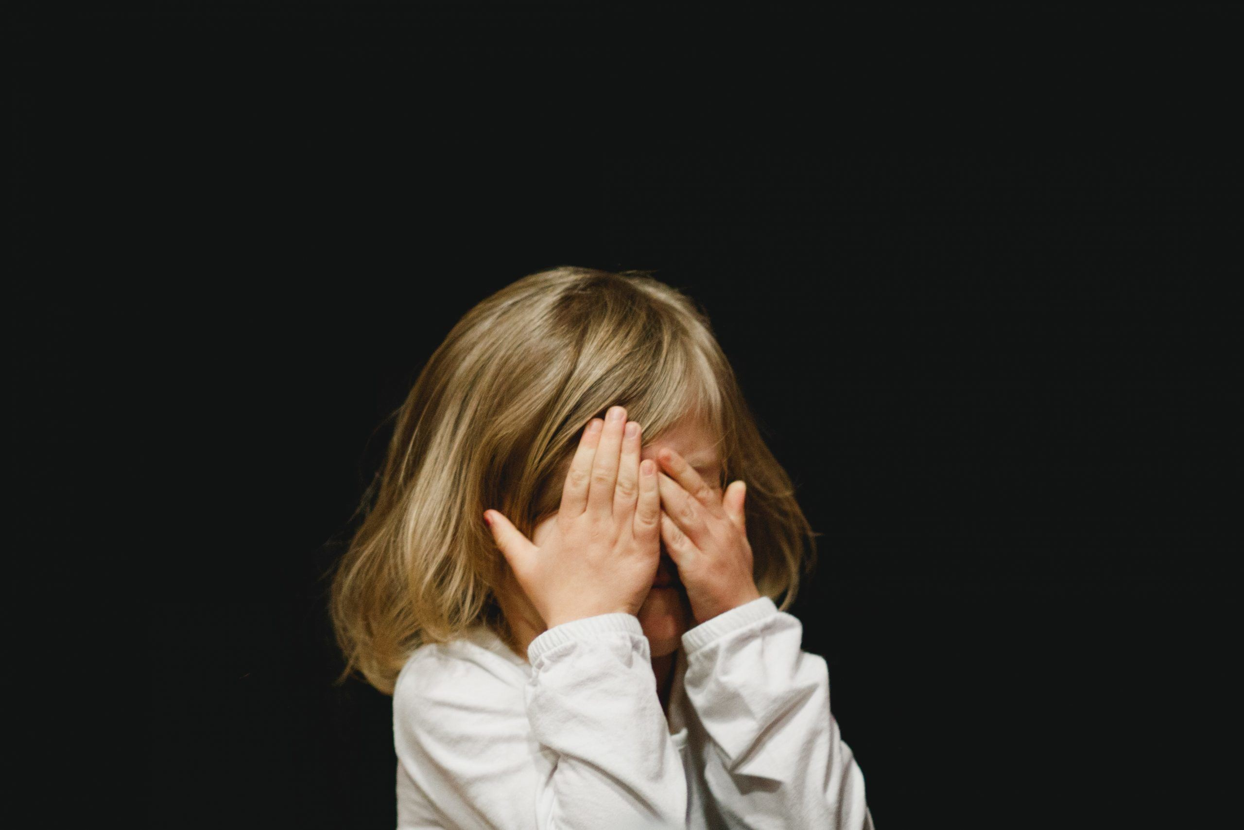 little girl hiding behind her hands